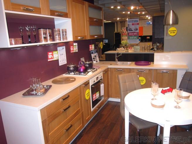 Propozycja kuchni z drewnianymi frontami szafek, białymi blatami oraz fioletowymi ...