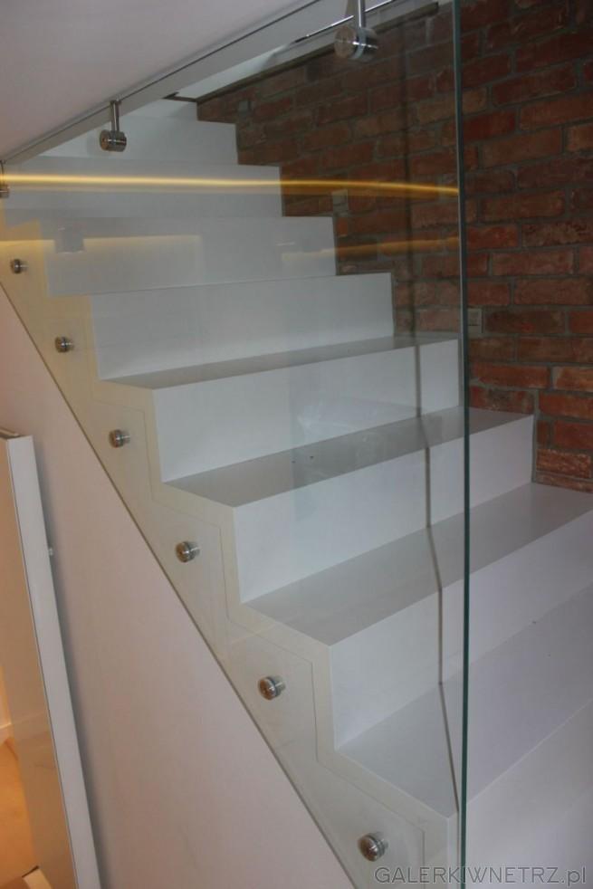 Proste schody całkowicie zabudowane. Z jednej strony znajduje sięszklana balustrada, ...