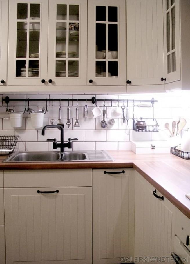 Białe drewniane szafki i białeMugaty - optycznie powiększają małe pomieszczenie