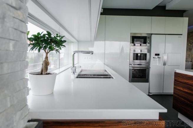 Blat kuchenny znajduje siępod wąskim, długim oknem. Blat jest biały Corian, ...
