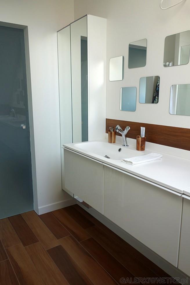 Piękna aranżacja łazienki w bieli i z brązową podłogą. Uwagę w tej łazience przyciąga ...