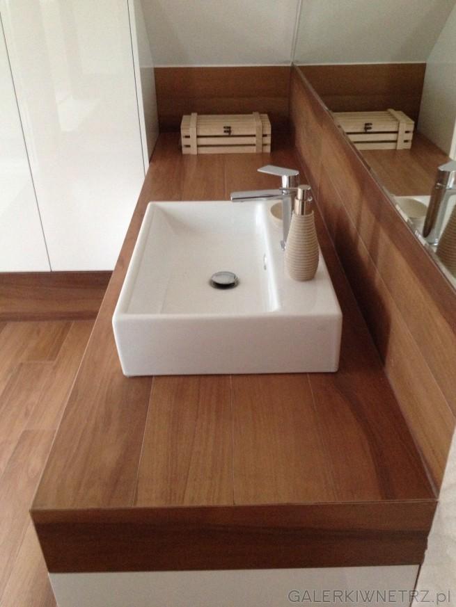 Prostokątna, biała umywalka położona jest na prostym blacie obudowanym płytkami ...