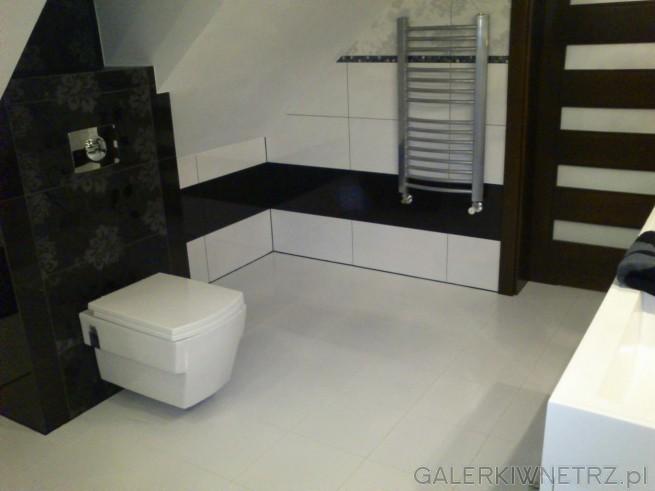 W łazience jest wykorzystana biała miska sedesowa o nowoczesnym kształcie, za ...