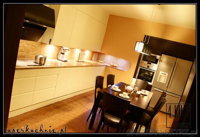 Duża kuchnia z centralnie umiejscowionym stołem i indywidualnie zaprojektowanym ...