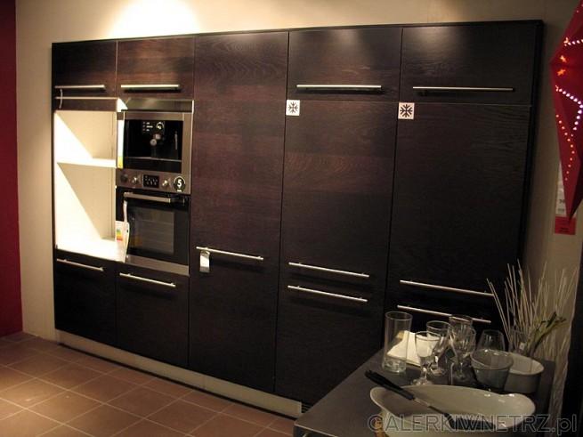 Zabudowa ściany w kuchni - ciemne panele. Lodówka do zabudowy, piekarnik i kuchenka ...