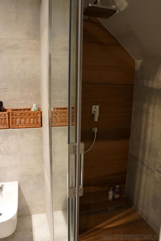 Płytki drewnopodobne pod prysznicem znajdująsię także na jednej ze ścian ...