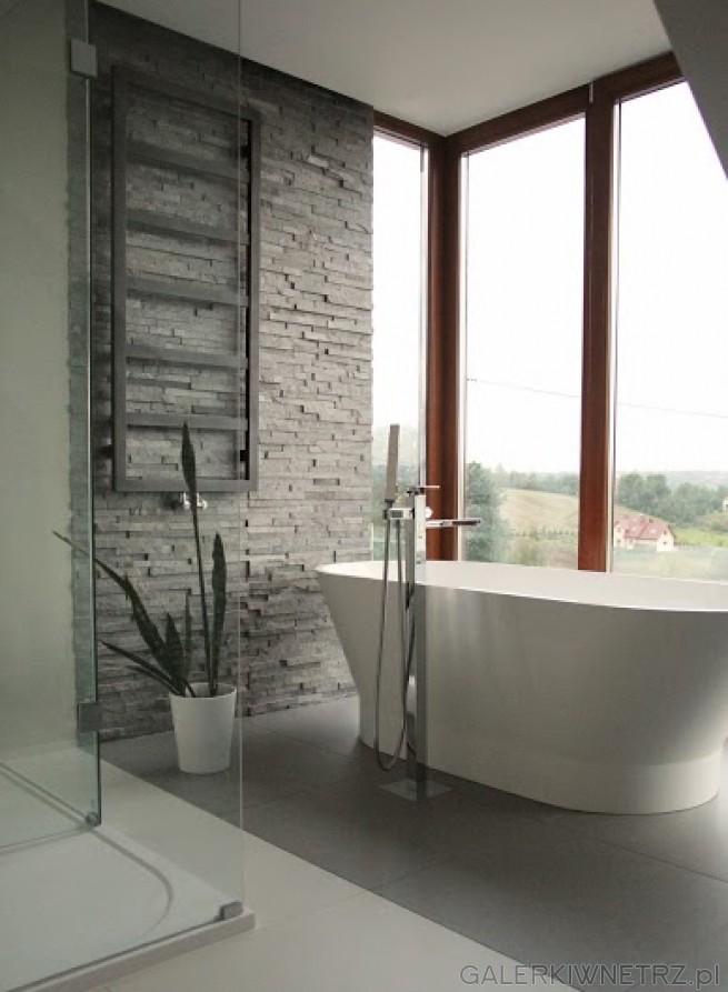 Gustowna aranżacja łazienki z wanną stojącą tuż przy dużym oknie. Za wanną ...