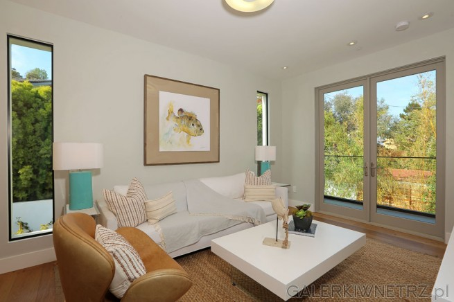 Niewielki salon, gdzie umieszczono białą kanapę oraz brązowy fotel. Na środku znajduje ...