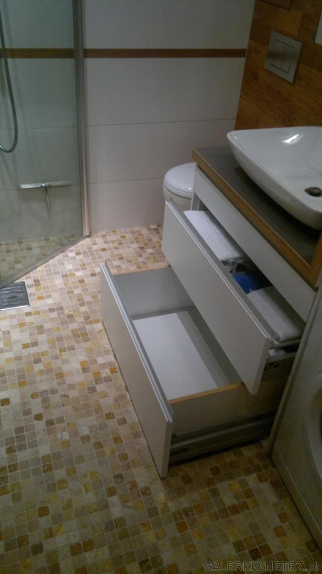 Pod umywalkąznajduje się biała szafka z dośćgłębokimi dwoma szufladami, idealnymi ...