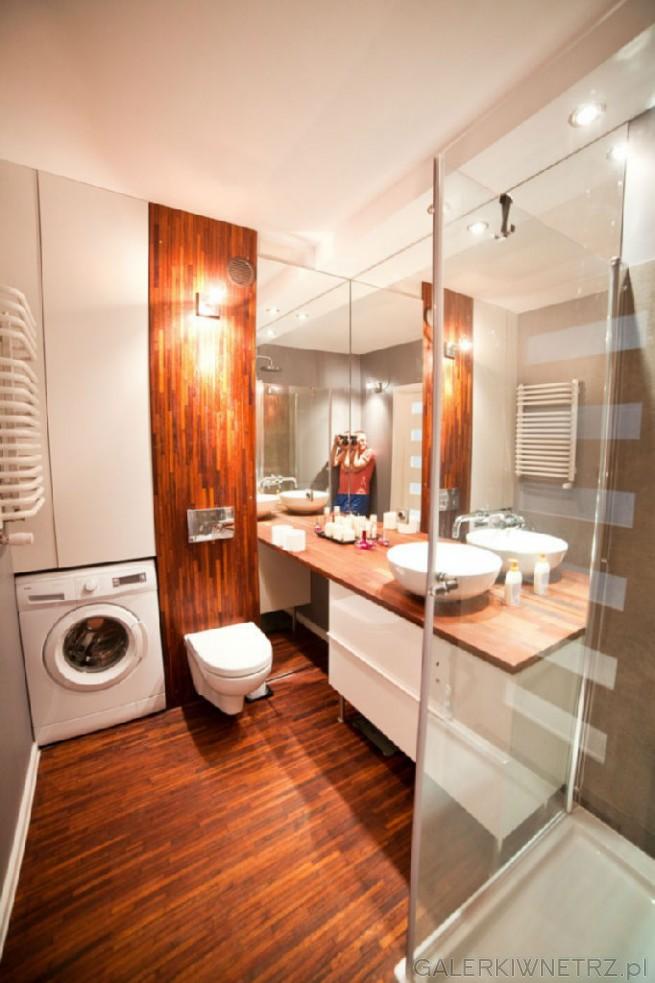 Aranżacja ślicznej łazienki, gdzie dominująbiele i drewno. Przez wykorzystany ...
