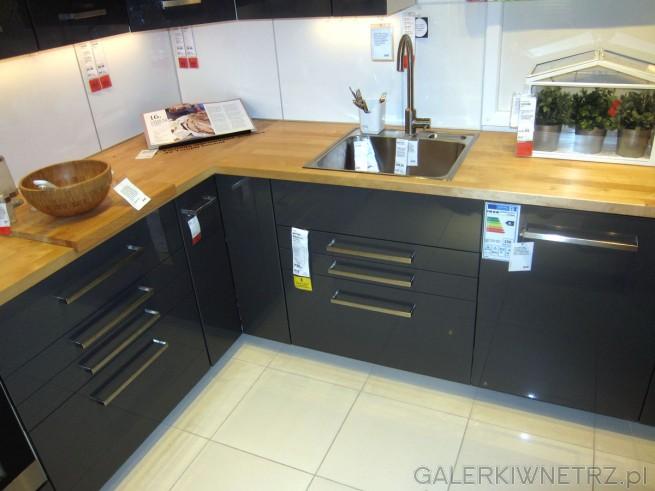 W tej kuchni ładnie kontrastująciemne szafki i szuflady z jasnobrązowym blatem. ...