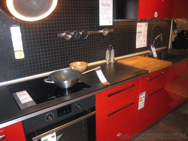 W tej aranżacji czerwonej kuchni znajdziemy czarną płytę indukcyjną z czterema ...