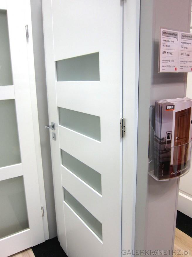 Białe drzwi wewnętrzne Koncept H.4 z czterema prostokątnymi przeszkleniami wykonanymi ...