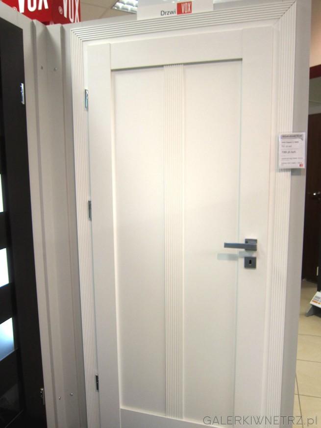 Białe drzwi wewnętrzne marki VOX, z ozdobnymi wgłębieniami, ozdobną framugą ...
