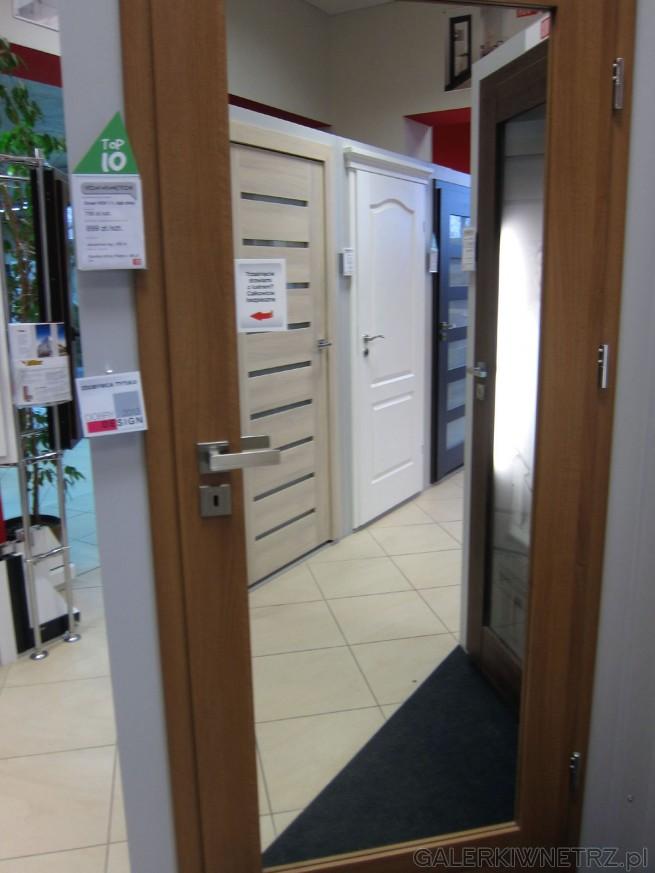 Drzwi wewnętrzne z brązową framugą, jednak wnętrze wypełnione jest lustrem. ...