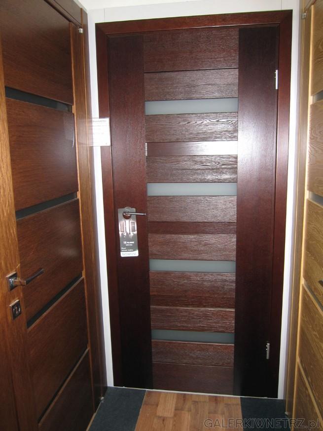 Drzwi wewnętrzne w kolorze ciemnego brązu, z czterema przeszklonymi prostokątami.