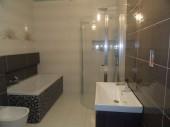 Jasna łazienka z fioletowymi dodatkami, mozaiką i płytkami z kolekcji Avangarde z Opoczna