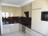 Aranżacja kuchni w kolorze ecru z białą podłogą i ciemnym blatem