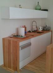 Biała mała kuchnia w kawalerce z płytami MDF i z blatem z klejonego jesionu