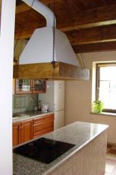 Rodzinna kuchnia w stylu wiejskim z ciekawym okapem kuchennym